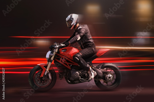 Fényképezés Motorcycle rider racing in red colors with motion blur