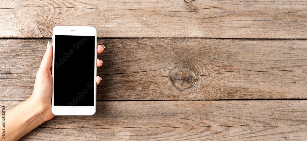 Fototapety, obrazy: Woman's hand holding white mobile phone with empty screen. Wooden background. Banner