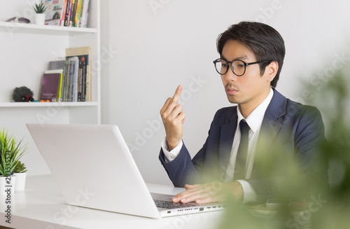 Valokuvatapetti Angry or Irritable Asian Businessman in Formal Suit Show Middle Finger in front