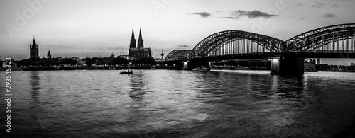 Black and white evening silhouette skyline landscape of the gothic Cologne Cathedra, Hohenzollern railway and pedestrian bridge, the old town and Great St Martin church in Cologne, Germany