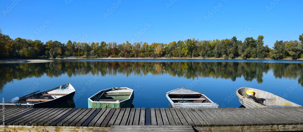 Fototapeta Autumn landscape with a lake, a boat bridge and some boats.