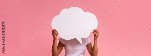 Black girl holding an empty speech bubble on pink background - 293552977