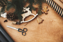 Christmas Rustic Flat Lay. Stylish Wrapping Paper, Wooden Reindeer, Gingerbread Cookies, Pine Branches,cones, Scissors, Thread On Rural  Table, Copy Space. Seasons Greeting Card Mockup