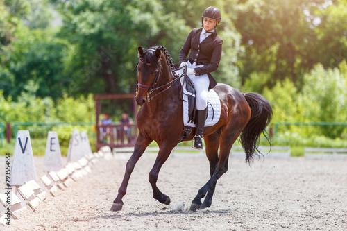 Young woman riding horse on dressage advanced test Fototapeta