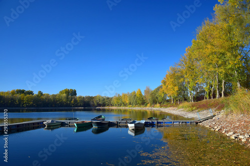Fotomural  Autumn landscape with a lake, a boat bridge and some boats.