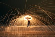 Male Adult Spinning Glowing Steelwool In Snowy Field Long Exposure Night Photo