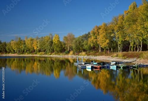 Fototapeta Autumn landscape with a lake, a boat bridge and some boats. obraz na płótnie