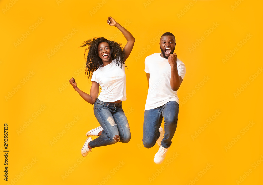 Fototapety, obrazy: Joyful black couple jumping up and down