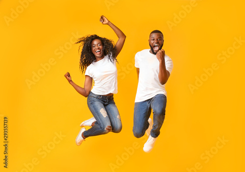 Joyful black couple jumping up and down Tablou Canvas