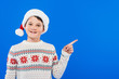 canvas print picture - front view of smiling kid in santa hat pointing with finger isolated on blue
