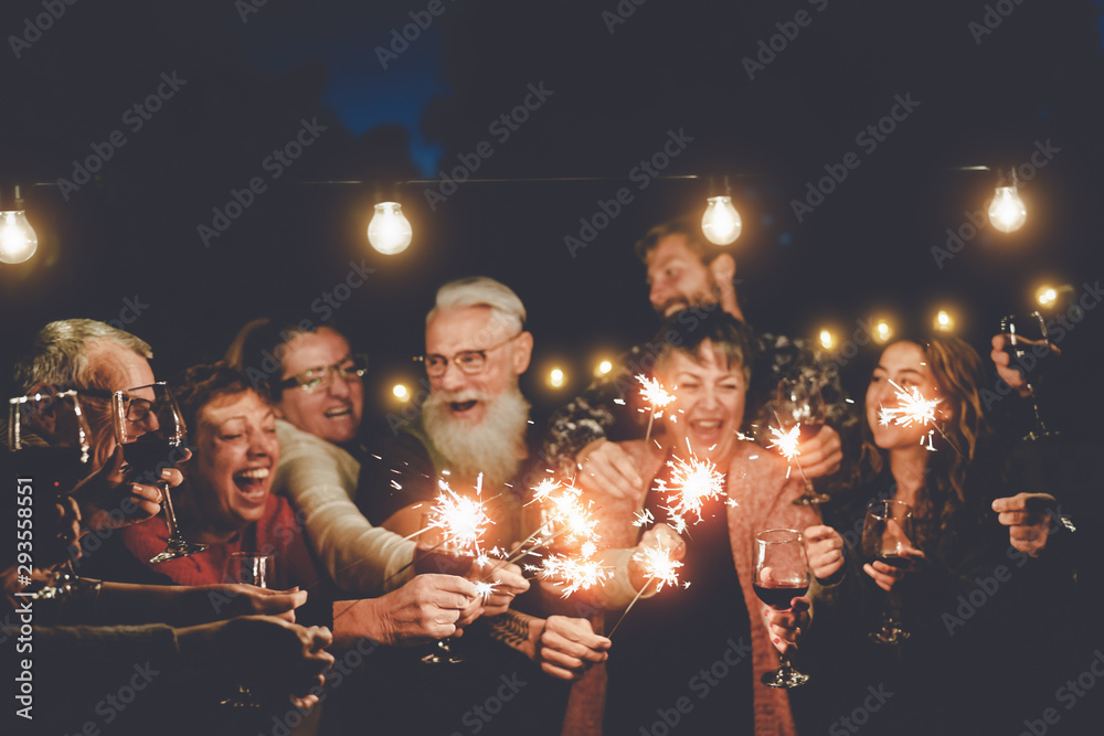 Fototapeta Happy family having at dinner party outdoor - Group of multiracial older and young people celebrating together drinking wine holding fireworks sparklers - Concept of youth and elderly parenthood