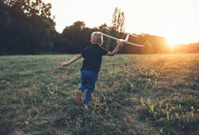 Rear View Of Boy Running With Glider Airplane Model For Takeoff
