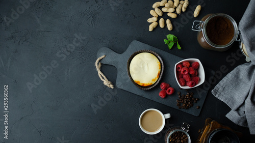Fototapeta Sernik z dodatkami. Maliny, orzechy, kawa. Widok z góry, ciemne tło. Miejsce na tekst. obraz