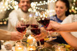 canvas print picture - holidays and celebration concept - close up of happy friends having christmas dinner at home, drinking red wine and clinking glasses
