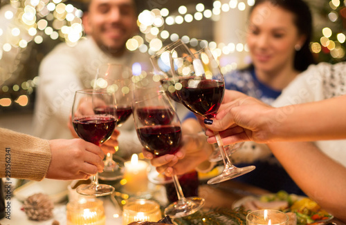 holidays and celebration concept - close up of happy friends having christmas dinner at home, drinking red wine and clinking glasses - 293562341