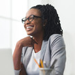 African American Businesswoman Laughing Sitting Against Window In Office