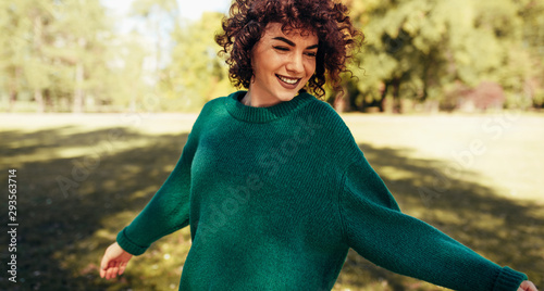 Horizontal image of beautiful young woman smiling posing against nature background with windy curly hair, have positive expression, wearing in green sweater Fototapete