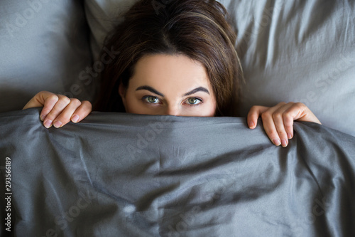 Obraz young beautiful woman lying in bed under blanket - fototapety do salonu
