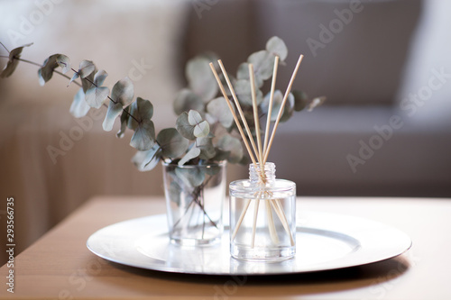 Fototapeta decoration, hygge and aromatherapy concept - aroma reed diffuser and branches of eucalyptus populus on table at home obraz