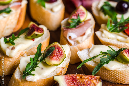 Traditional tapas from spain or italian bruschetta with cheese, meat and figs. Party food on catering platter.