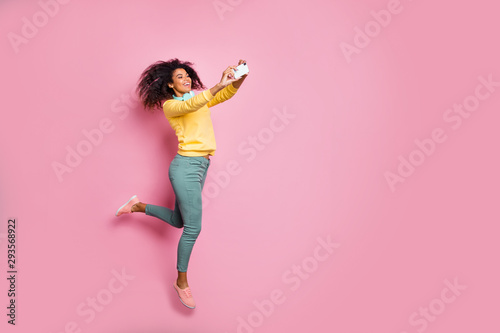 Travel motion lifestyle people modern technology concept. Full photo of cheerful carefree excited trendy style girl making self-portrait jumping wear yellow sweatshirt pants isolated pink background - 293568922