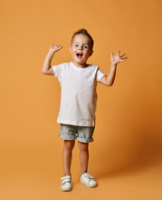 Happy Screaming Boy Kid In White T-shirt, Blue Jeans Shorts And White Sneakers Yelling With His Hands Up On Yellow