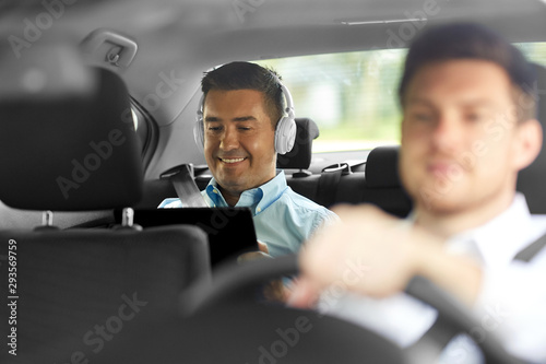 transportation, taxi and technology concept - smiling middle aged male passenger with tablet pc computer and headphones on back seat and car driver - 293569759