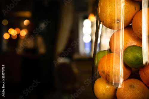Fotografie, Obraz  Oranges and lime in a tall glass glass backdrop in warm dark shades blurry