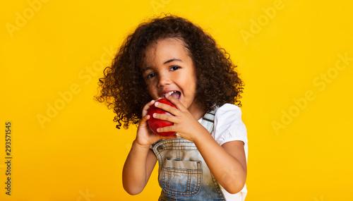Vitamin snack. Little girl biting red apple - 293571545