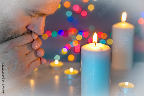 Fotografie, Obraz  Distraught man with folded hands praying or meditating by a lighted candle