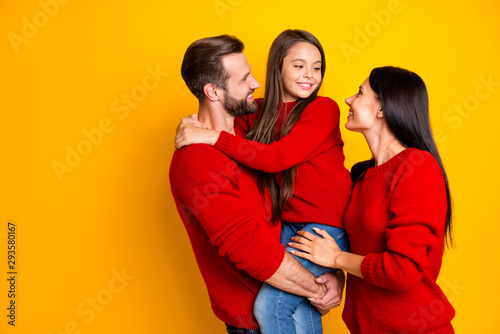 Photo of cheerful charming cute family with mommy and daddy embracing their daug Canvas Print