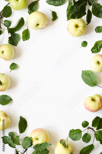 Fresh apples green leaves on white wooden background