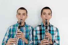 Two Children Playing The Clarinet On White Background. Two Twin Brothers Play Wind Musical Instruments