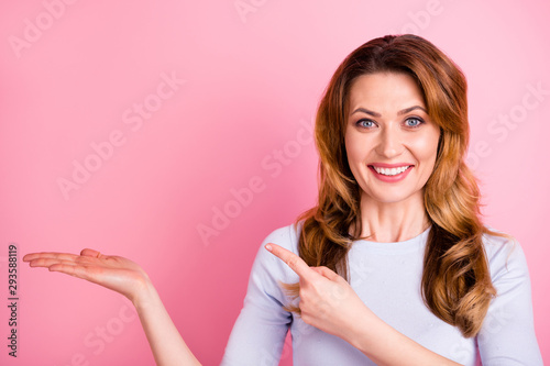 Portrait of pretty cheerful positive promoter hold hand point index finger at copy space demonstrate promotion adverts wear good looking outfit pullover isolated over pastel color background - 293588119