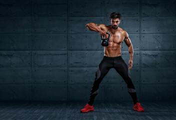 Handsome Bodybuilder Exercising With Kettlebell. Copy Space for text