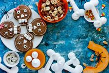 Halloween Sweets And Treats - Skull Cookies, Candy Corn, Pumpkin Panna Cotta, Meringue Bones Top View