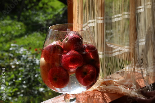 A vase of red apples in drops of water on the glass stands on the window of a village house in the rays of sunset against the background of the garden and curtains.Selective focus on the fruit bowl