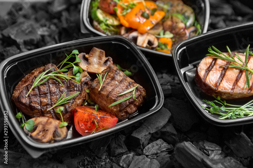 Composition of three grilled dishes in to go boxes