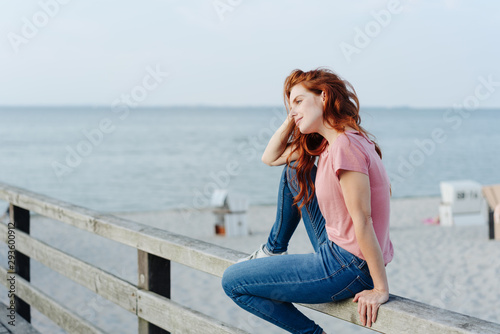 obraz lub plakat Casual young woman sitting on a pier railing