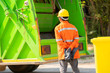 Leinwanddruck Bild - Garbage removal worker in protective clothing working for a public utility emptying trash container.