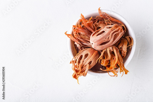 Fototapeta Dried whole mace in a bowl on white concrete background close-up with copyspace. obraz
