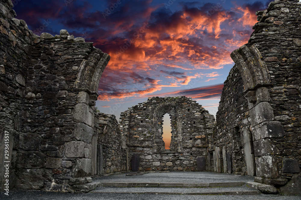 Fototapeta Monastic cemetery of Glendalough, Ireland. Famous ancient monastery while sunset in the wicklow mountains with a beautiful graveyard from the 11th century