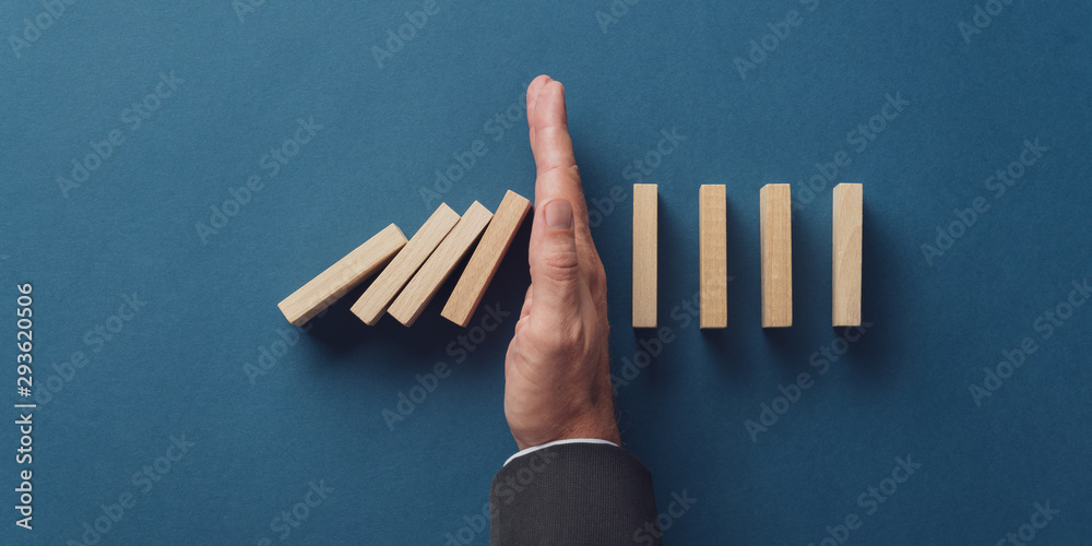 Fototapeta Business crisis manager stopping falling dominos from collapsing