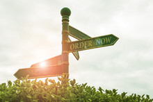 Text Sign Showing Order Now. Business Photo Showcasing Service Restaurants Or Stores Provide To Get What You Need Home Green Road Sign On The Crossroads With Cloudy Sky And Green Grass In The