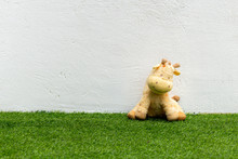 Stuffed Animals Sitting On The Grass Against A White Wall