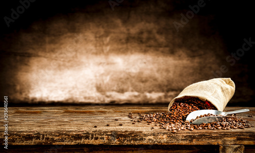 Fresh old sack of coffee grains and brown old wall background