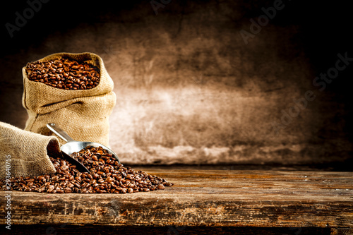 Fotografering Fresh old sack of coffee grains and brown old wall background