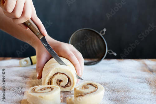 Photo Woman's hands cutting homemade cinnamon roll dough over a floured surface with duster in background