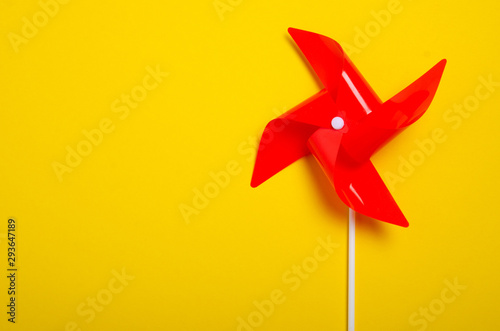 Photo Red windmill on yellow background, top view