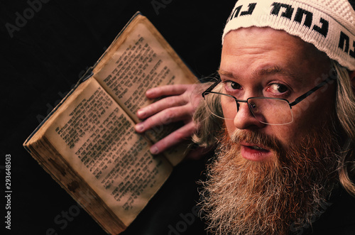 Fototapeta A Hasidic Jew reads Siddur. Religious orthodox Jew with a red beard and with pace in a white bale praying. On the bale is an inscription Rabbi Nahman from Uman. Closeup obraz